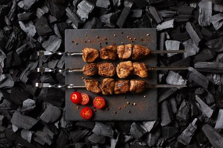 Shish kebab on skewers. Three portions of grilled meat on a stone plate, spicy and cherry tomatoes. Charcoal background. Top view. Imagens - 148937240