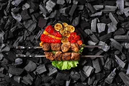 Shish kebab on skewers and grilled vegetables - sweet pepper, zucchini, cherry, tomato on a round plate. Charcoal background. Top view.