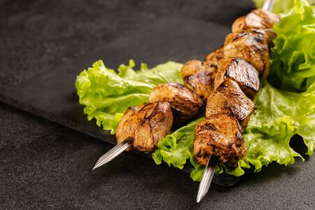Two portions of shish kebab on a stone plate with salad. Serving in a restaurant. Imagens