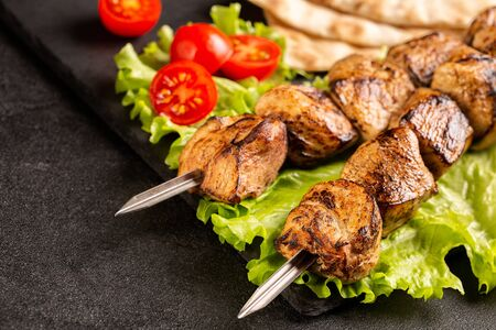 Two portions of shish kebab on a stone plate with salad, sliced pita bread, cherry tomatoes. Serving in a restaurant. Imagens