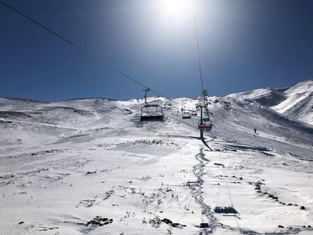 Ski lift in the ski resort of Erciyes, Turkey. Beautiful relief, bright sun, snowy slopes. Imagens - 150394514