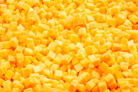 Frozen diced pumpkin. Food background of freshly frozen diced pumpkin. Frame filled with pumpkin. Top view. Concept: Food products for long-term storage.