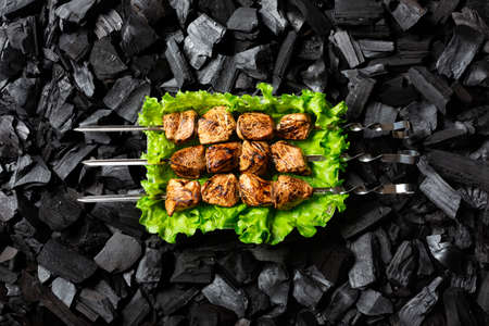 Ready shish kebab. Grilled meat on skewers in an aluminum foil disposable container with salad. Charcoal background. Top view.