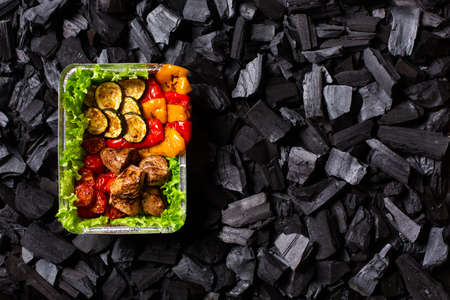 Ready shish kebab. Portion of grilled vegetables - sweet pepper, zucchini, cherry, tomato and meat in a aluminum foil disposable container on charcoal background. Top view. Copy space.