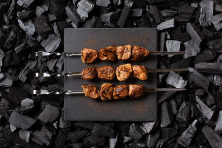 Shish kebab on skewers. Three portions of grilled meat on a stone plate. Charcoal background. Top view. Imagens