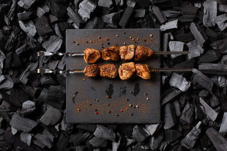 Shish kebab on skewers. Two portions of grilled meat on a stone plate. Charcoal background. Top view.