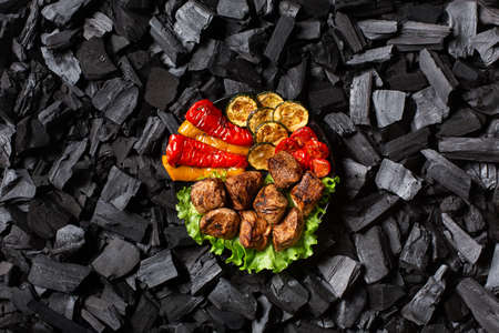 Shish kebab and grilled vegetables - sweet pepper, zucchini, cherry, tomato on a round plate. Charcoal background. Top view.