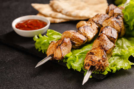 Two portions of shish kebab on a stone plate with salad. Hot sauce, sliced pita bread. Serving in a restaurant.