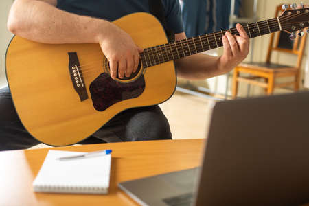 Man learns to play the guitar using online video lessons. The concept of remote communication and education.