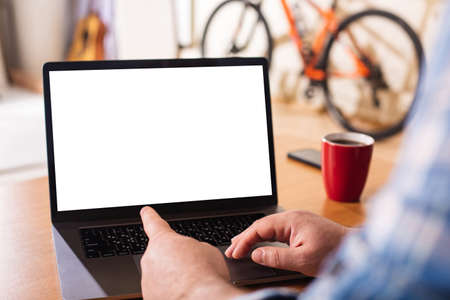 A laptop with a blank white screen on the background of a home environment. The finger of a man's hand points to the laptop screen. Concept: Remote work at home. Imagens