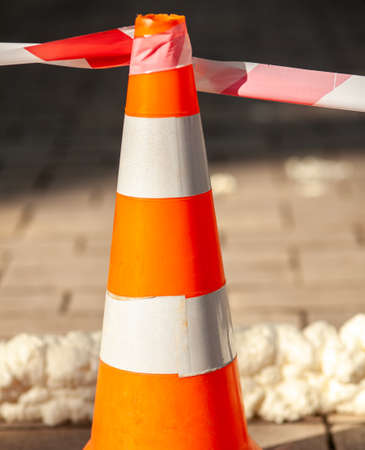 Traffic cone with red white caution tape.