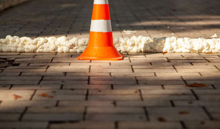 Red white traffic cone on the sidewalk. Imagens