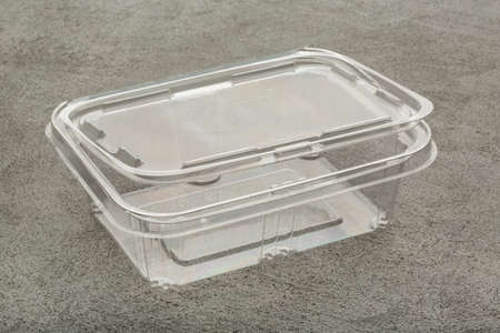 Disposable plastic transparent lunch box on a gray background.