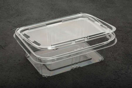 Disposable plastic transparent lunch box on a black background.