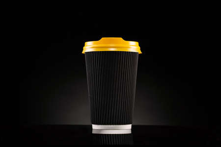 Disposable corrugated cardboard cup with yellow lid on a black background. Cup for cappuccino, latte or coffee. Coffee to go.