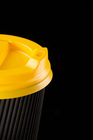 A fragment of a disposable corrugated cardboard cup with yellow lid on a black background. Cup for cappuccino, latte or coffee. Coffee to go.