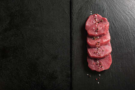 Raw Beef Medallions on a kitchen cutting board.