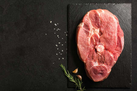 Uncooked Pork Ham steak on a stone kitchen cutting board. Imagens