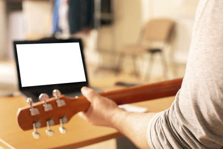 Man learns to play the guitar using online video lessons.
