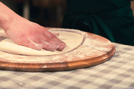 Kneading the pizza dough. Pizza master class in a pizzeria.