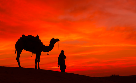 nomad: Rajasthan desert with dramatic sky with camel and man Stock Photo
