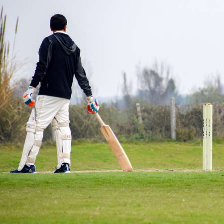 New Delhi India – March 3 2020 : Full length of cricketer playing on field during sunny day in local playground, Cricketer on the field in action, Players playing cricket match at field Editorial