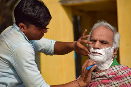 New Delhi, India - March 04, 2020: Handsome old man shaving his beard in bathroom during morning time at Yamuna river ghat in New Deli, India, Yamuna Ghat View