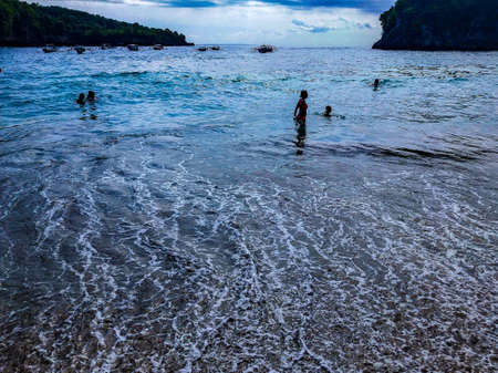 Picturesque ocean cove of Crystal Bay at sunset. Crashing waves, anchored boats, colorful sunset, tropical vibes located off the western coast of Nusa Penida, an island southeast of Bali, Indonesia