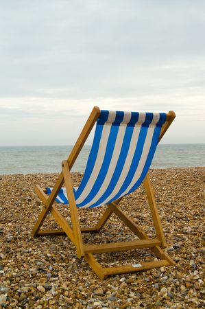 Blue and white striped deckchair on a pebble beach by the sea