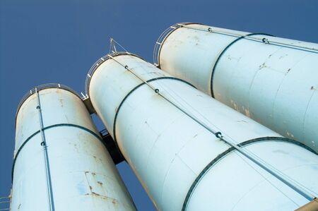 Three industrial light blue silos against blue sky