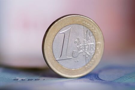 Euro coin standing on euro notes, with shallow depth of field Stock Photo