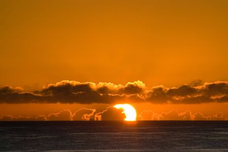 Sunrise over the sea through low clouds