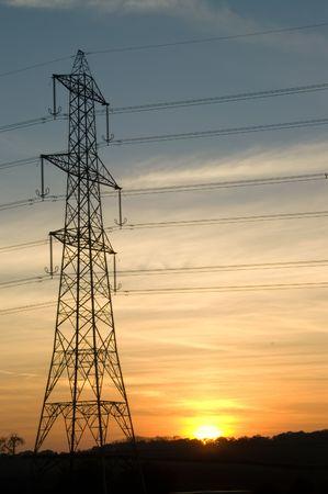 Electricity pylon at sunset against orange sky