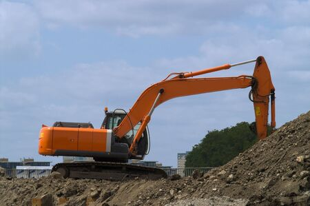 Orange digger at work excavating soil against blue sky with white clouds