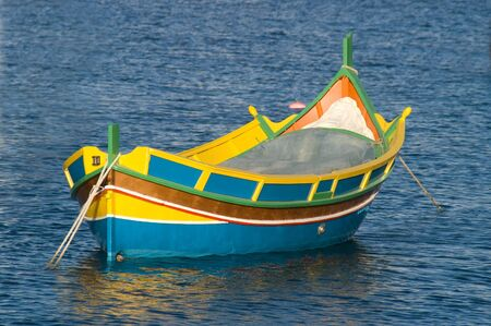 Luzzu, colourful traditional Maltese fishing boaton blue water with ripples