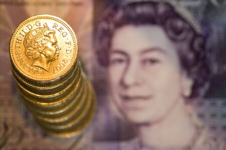 Stack of one pound coins on a blurred bank note Stock Photo