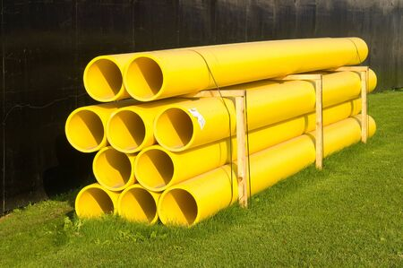 Yellow plastic construction pipes stacked on green grass photo