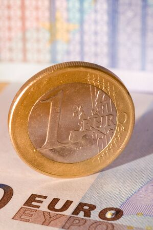 Euro coin against a slightly blurred euro note