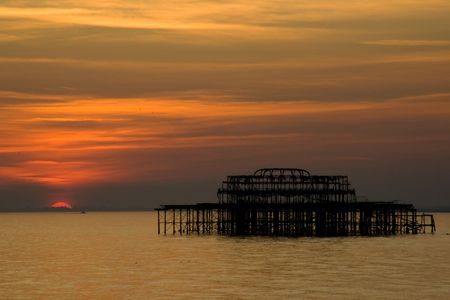 Silhouette of ruins of Brighton pier at sunset Stock Photo