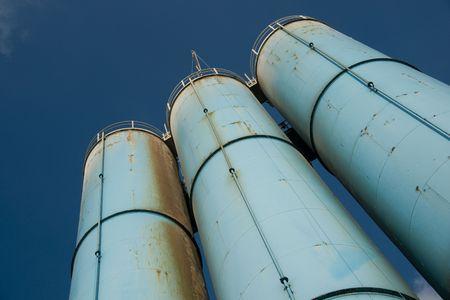 Three blue rusty industrial silos against deep blue sky