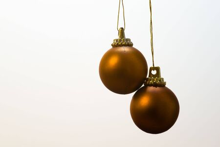 Pair of golden Christmas baubles isolated on white