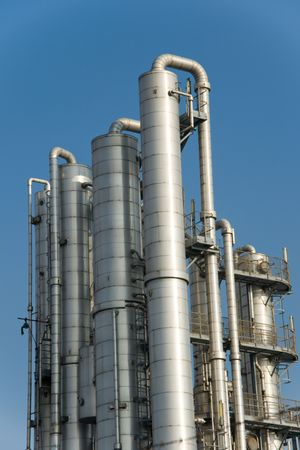 Distillation columns at industrial plant or refinery against deep blue sky Stock Photo