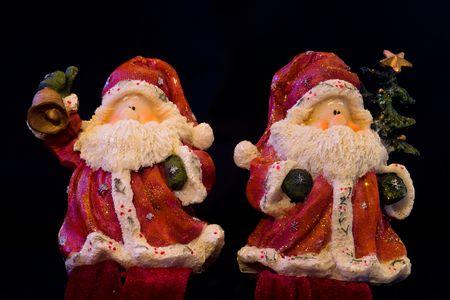 Pair of Santa Claus figurines isolated on black