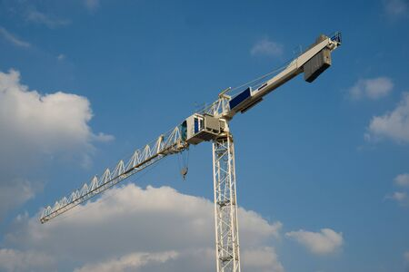 White construction crane against blue sky with fluffy white clouds
