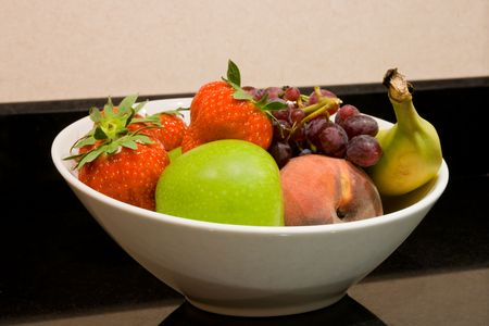 Close up of white fruit bowl with apple, strawberries, peach, banana and grapes