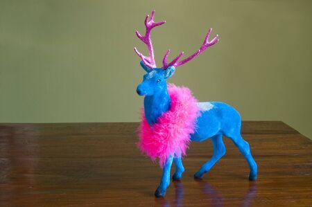 Christmas decorative pink and blue glitter stag on wooden table Stock Photo