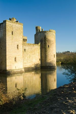 mote: Bodiam castle with reflection on mote against blu sky