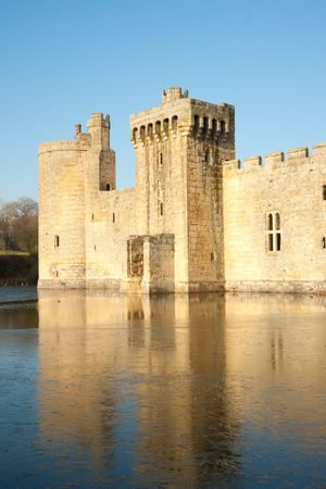 mote: Ancient castle with mote and reflection against clear blue sky