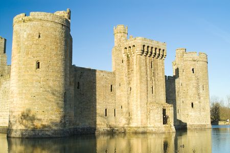 Bodiam Castle with mote and reflection against clear sky, Kent, England