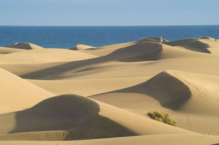 gran canaria: Sand dunes and sea against clear blue sky Stock Photo